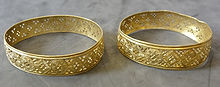 Two gold bracelets. They have the same geometric pattern, made by piercing many small holes into the gold