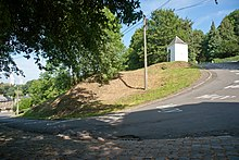 Vue d'une ascension cycliste et d'un virage vers la gauche. Une chapelle est visible sur l'image.