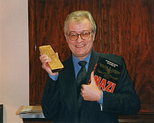 Sayer holding a book and a bar of gold
