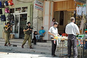 Israeli–Palestinian conflict in Hebron - Open-air market in city being patrolled by Israeli troops (2004)
