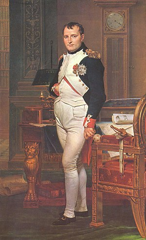 Full length portrait of Napoleon in his forties, in white and dark blue military dress uniform. He stands among rich 18th-century furniture. They have papers on them. He looks at the viewer. His hair is Brutus style, cropped close but with a short fringe in front. His right hand is in his waistcoat.