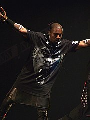 A man holding a microphone in his right hand whilst on stage. He wears a black T-shirt with a tiger-like face on it, tight leather pants, and a kilk.