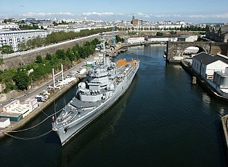"Brest Arsenal - The helicopter-carrier Jeanne d'Arc docked on the left bank of the Penfeld, downstream of the pont de l'Harteloire.  The high-tides are too low for ships to be able to dock nearer to the quays, which are still all along the river.  In the background, the église Saint-Louis, to the right, the viaduct of the ""grue revolver"", a former crane that looked like a pistol."
