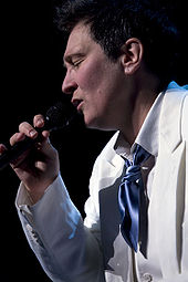 A woman wearing a white suit with her eyes closed, holding a microphone.