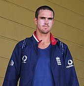 An English cricketer with closely cut dark brown hair, in a dark blue jacket.  He is wearing a blue T-shirt and has sun-cream on his cheeks.