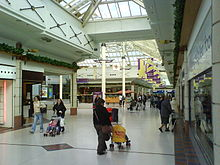 Shopping mall thoroughfare with two storey glazed roof and white marble flooring lined on either side by rows of shops