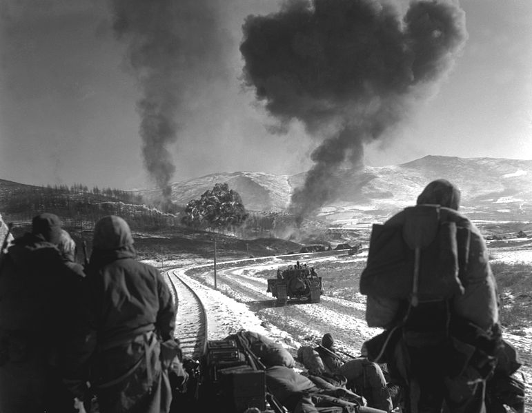 U.S. Marines watch explosions of bombs dropped by Marine Vought F4U Corsairs during the Battle of Chosin Reservoir, Korea, in December 1950.