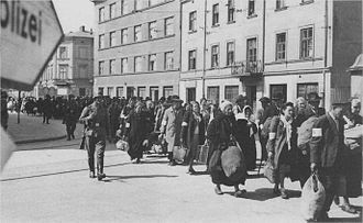 "The Holocaust in Poland - Liquidation of Kraków Ghetto, March 1943. Families walk to Prokocim railway station for ""resettlement"".  Destination: Auschwitz."