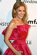 Kylie Minogue in a pink dress smiling.