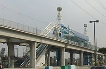An elevated train station and two train tracks. The station has a blue roof and is made of white metal.