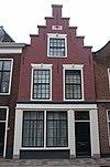 foto van Pand met trapgevel, drie vensters door strekken met maskersluitstenen afgedekt. Onderpui verbouwd