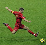"Steven Gerrard wearing a football kit, about to strike a ball. On his forearm, he is wearing an armband; the letter ""C"" to represent ""Captain"" is visible."