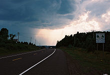 a highway curving over the crest of a hill flanked by telephone poles on either side. There is a white road sign on the right side of the road and storm clouds in the sky.