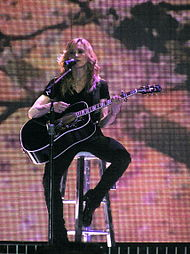 Faraway image of a blond woman singing in front of a bloomy backdrop. She is wearing a black blouse and pants of the same color. She is holding a black guitar and a microphone to her mouth.