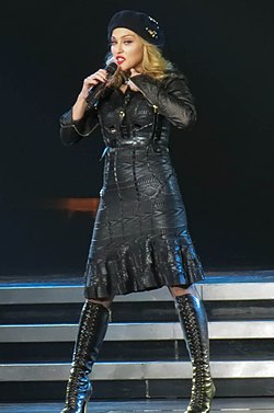 Madonna in a black leather jacket, skirt and a French cap on her head. She sings into a microphone held in her right hand