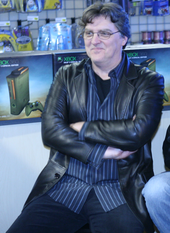 A men wearing black leather jackets is sitting in a chair, surrounded by Halo-themed Xbox 360s and accessories.