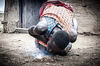 Fire making - Maasai warrior lighting a fire.