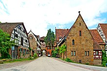 Photograph of the gate (left of center, background) and flanking buildings. The closest, on the right, is the Frühmesserhaus.