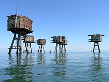 The view from a boat of a site containing six sea forts. The forts have an octagonal shape, with rusty metal walls and two rows of windows. Each fort is supported by four legs jutting from the sea at an angle.
