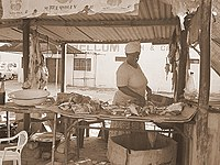 Woman selling meat, one of the many trades in the town.