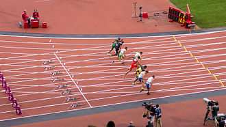Jason Smyth (in lane five) breaking the men's T13 world record at the 2012 Paralympic Games in London. Men's 100m T13 Final, 2012 Paralympics.jpg