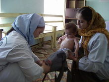 Woman with infant attending maternal health clinic in Afghanistan