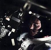 Photographie en couleur de Michael Collins dans le module de commande et de service avec le visage partiellement éclairé.