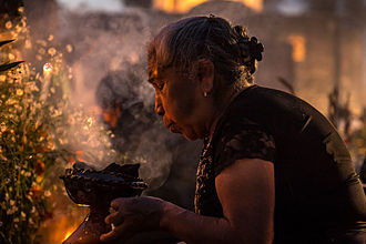 "Day of the Dead - Woman lighting copal incense at the cemetery during the ""Alumbrada"" vigil in San Andrés Mixquic"