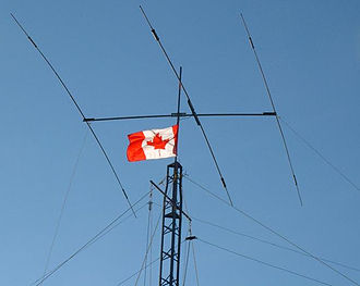Amateur radio - The top of a tower supporting a Yagi-Uda antenna and several wire antennas, along with a Canadian flag