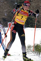 A woman cross country skis uphill towards the camera, holding a red ski pole in each hand. She wears black winter sportswear, a red cap and a yellow jersey with the number 7. A second skier behind her can be seen on the left.