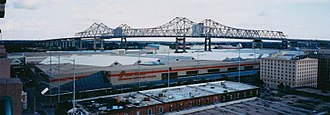 New Orleans Morial Convention Center - The New Orleans Morial Convention Center, and in the background, the Crescent City Connection bridge over the Mississippi River.