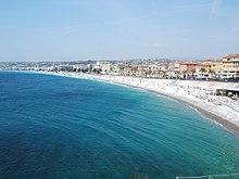 Vue orientée ouest depuis un quai de la baie et de la plage de Nice.