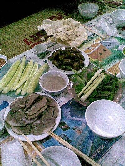 Thịt chó luộc, dồi chó dùng kèm với rau sống & mắm tôm tại một quán thịt chó bình dân ở miền Bắc Việt Nam.
