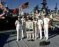 Officers from the guided missile cruiser USS PRINCETON (CG 59) gather around a framed portrait of their ship while standing on the dock in front of the guided missile frigate USS RE - DPLA - dc426e7c268eaff15ae7866b25133b1b.jpeg