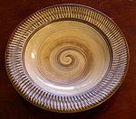 A plate with a spiral pattern in the middle and a stripe pattern along the rim.