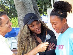 A reporter holding a microphone to Osaka with Williams to the side smiling