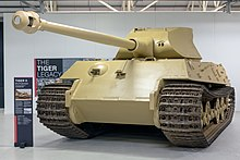 A frontal view of a large, pale-yellow tank in a white museum gallery.. Its curved-faced turret is pointing forwards, the long gun overhangs the front by several meters.