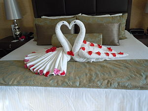 Decorative folding - Peacock and peahen towel animals in a resort suite. Items like the flower petals and eye stickers here can be used to accentuate a design.