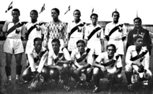 Photo of twelve men, seven standing and five crouching, inside a stadium