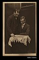 Photographic postcard of two men at a small table reading a 'The Daily Mirror' newspaper (9910386534).jpg