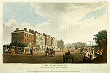 Bildo de Piccadilly en 1810 montrantaj domoj, trejnistoj kun ĉevaloj kaj piedirantoj