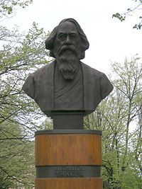 """A cylindrical wood-trimmed plinth supports a bust of a bearded man in his sixties. On the plinth, a plate reads """"Rabindranath Thakur""""."""