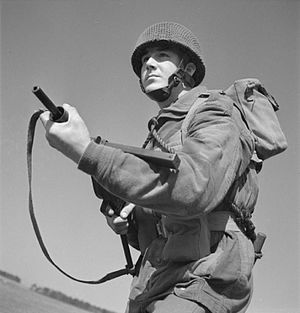 8th (Midlands) Parachute Battalion - 8th Parachute Battalion soldier armed with the Sten submachine gun, he has a toggle rope around his neck and is wearing the airborne forces steel helmet and the Denison smock May 1943.