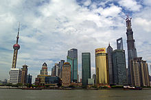 A group of skyscrapers and towers, seen from across a river. At the left is one consisting of a sphere on concrete supports topped by a long spike; in the center are smaller buildings, one a bright gold color, gradually rising to the tallest one at right, still under construction