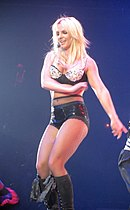 A female blond performer. She is leaning against a pole, grabbing it with her right hand. She is wearing a black sparkly bra, high-waisted shorts and laced-up high-heeled boots with fishnet stockings.