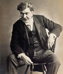Black-and-white photographic portrait of Rafael Bordalo Pinheiro sitting on a chair.