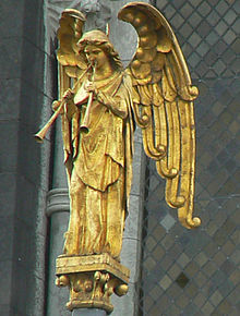 Robed figure of a standing winged angel with two straight trumpets, gazing down.