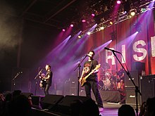 Rise Against performing on stage. Three band members can be seen, while the fourth is partially obscured.