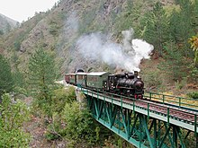 Steam engine pulling wooden passenger cars over a bridge