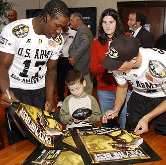 2007 Texas Longhorns football suspensions - Sergio Kindle (left) signing autographs for children from the Warm Springs Rehabilitation Center in San Antonio in January 2006.